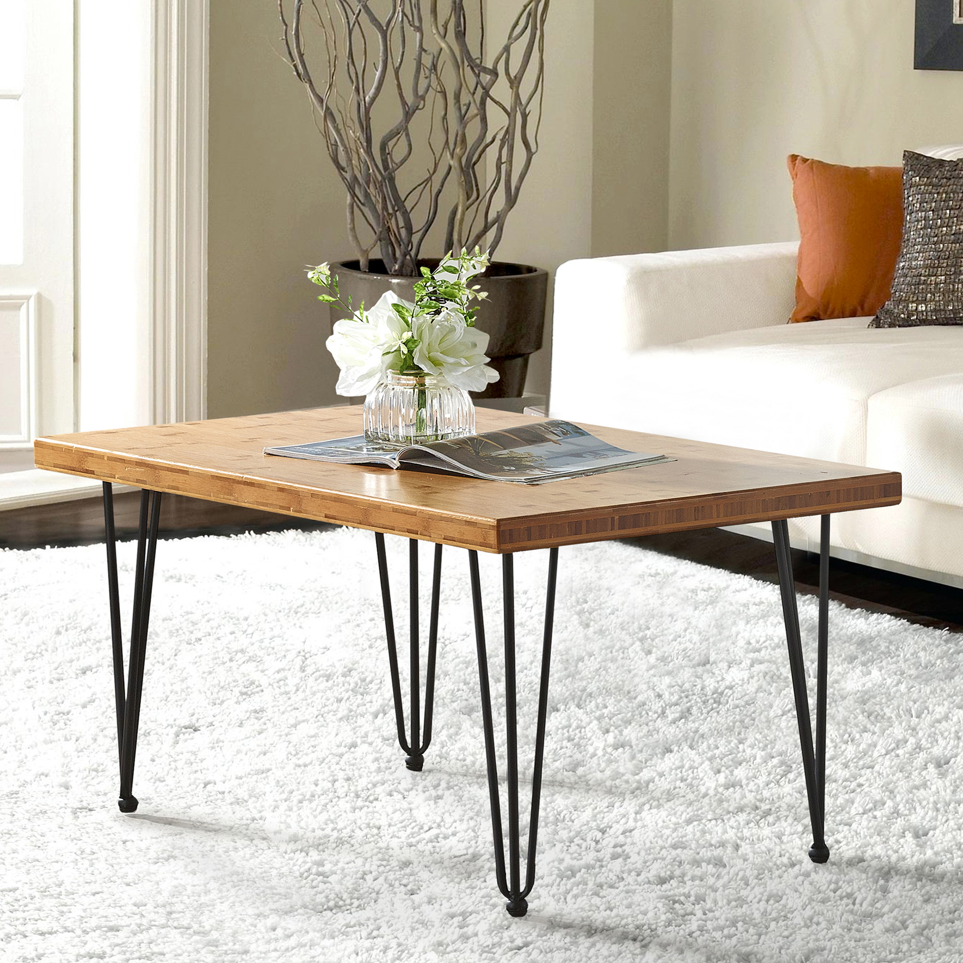 White flowers and open magazine on wood center table with thin metal legs