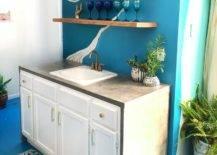Wine glasses on open shelves above sink