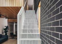 Wiry-mesh-styled-staircase-leads-to-the-top-level-of-the-home-with-bedrooms-92216-217x155