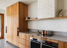 Wooden-cabinets-for-the-single-wall-kitchen-with-white-painted-brick-backsplash-74858-217x155