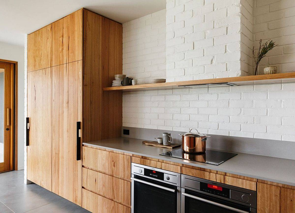 Wooden cabinets for the single-wall kitchen with white-painted brick backsplash