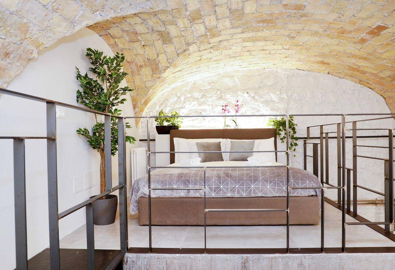 loft style bed with open brick cathedral ceiling