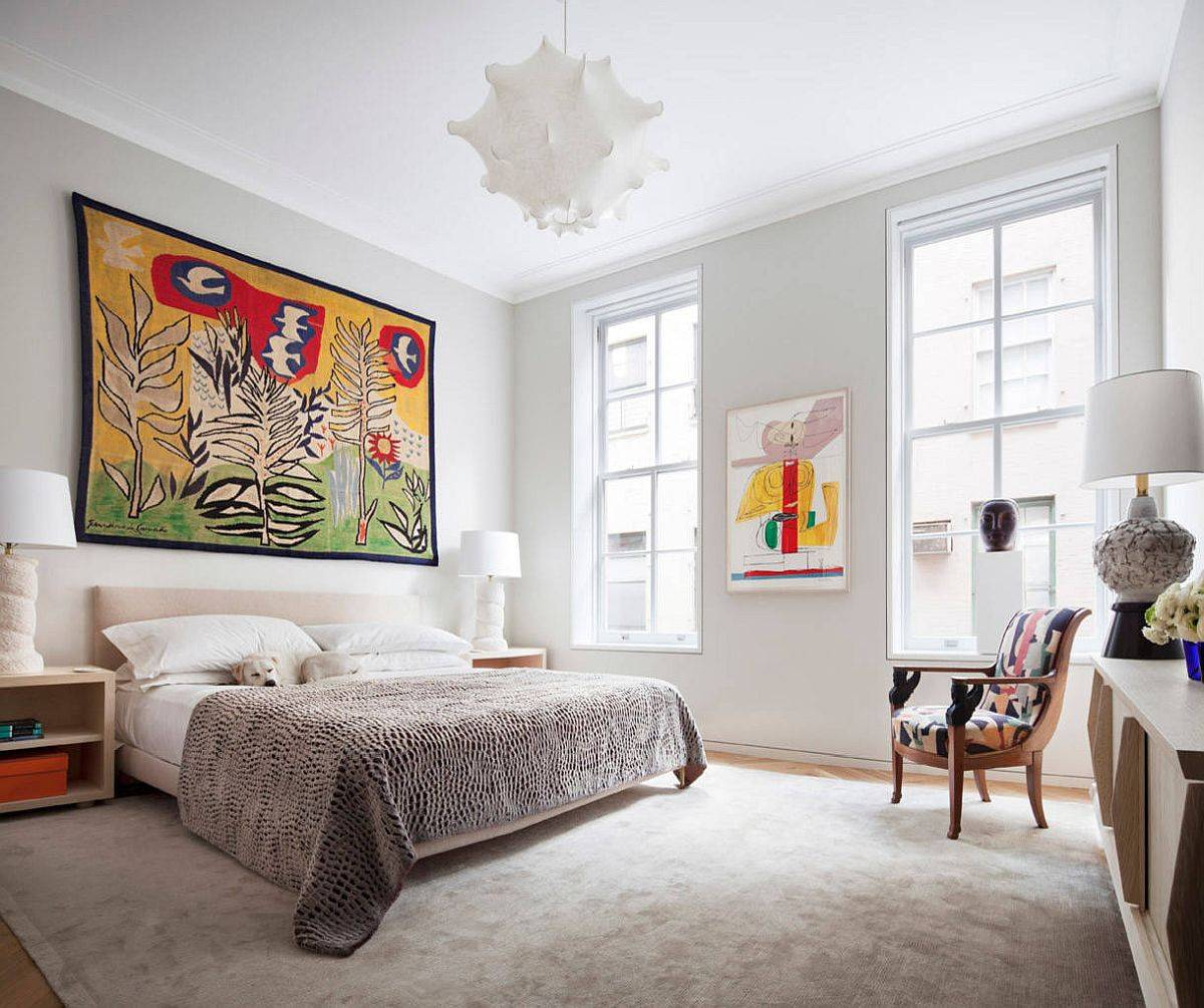 Beautiful and relaxing bedroom of the Tribeca home with white backdrop and eye-catching, colorful wall art