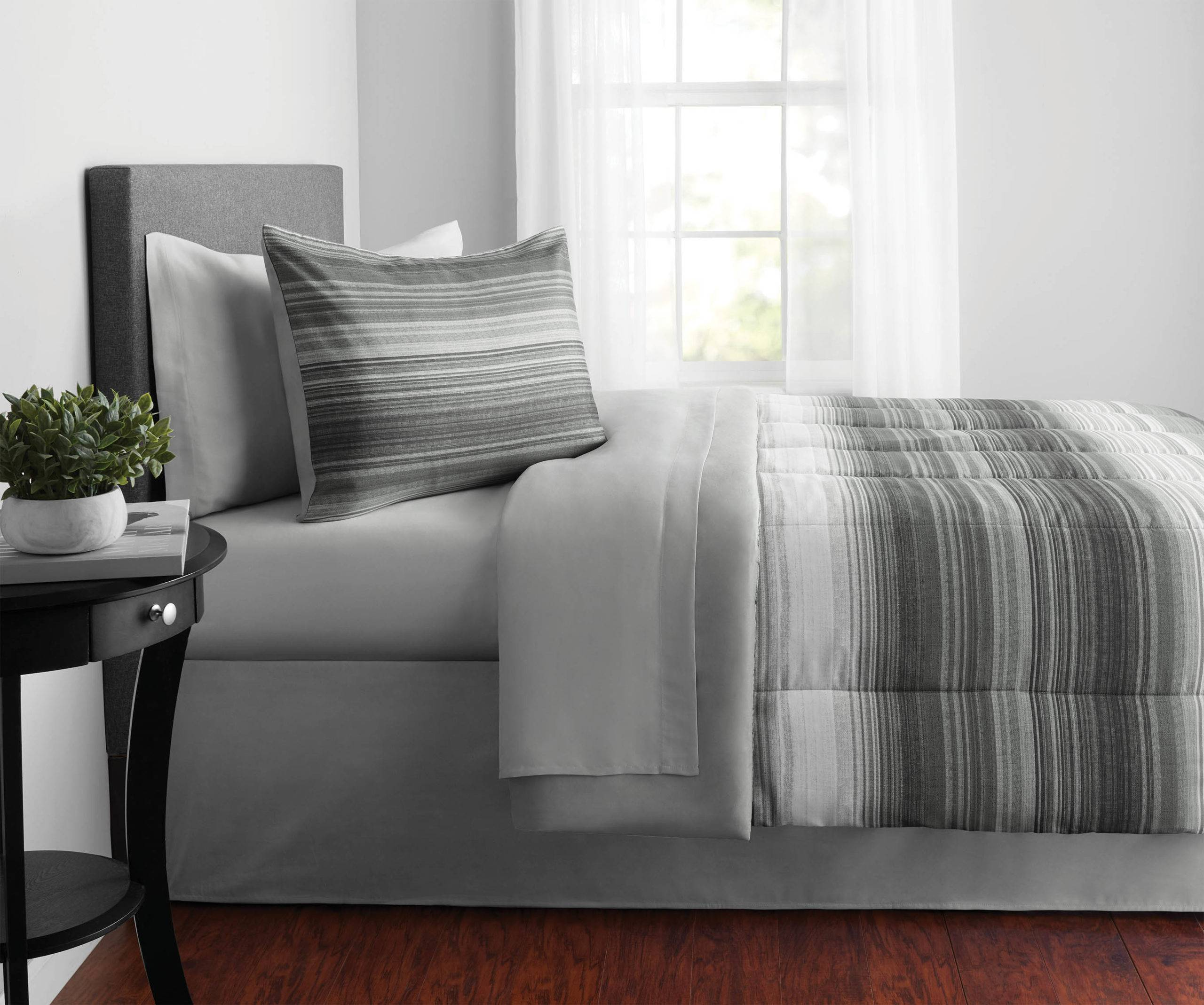 Bed covered in grey sheets with potted plant on the bedside table