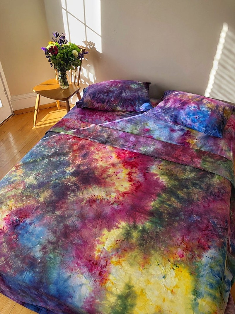 Bed with tie dye sheets and pillows beside a vase full of flowers