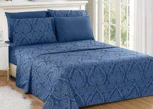 Blue printed bedsheets on bed with overhead round mirror