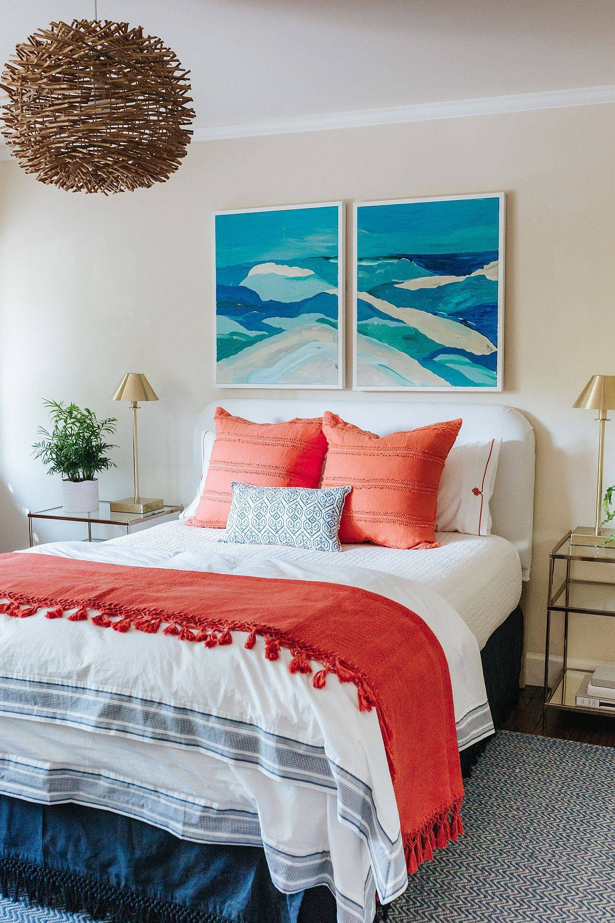 Bold-and-bright-coral-accent-pillows-along-with-blue-wall-art-steals-the-show-in-this-bedroom-11846