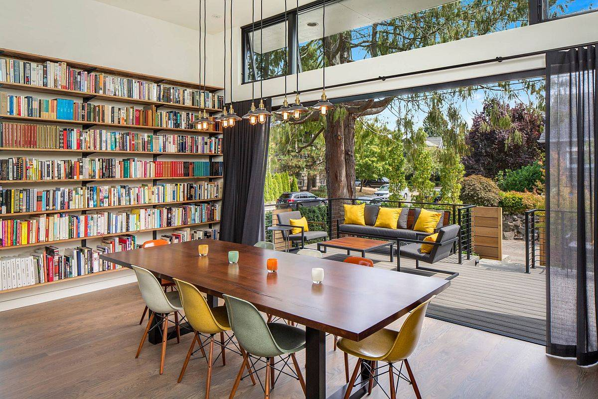 Bookshelves in the corner along with a deck and sitting area turn this dining space into a fun family and reading room