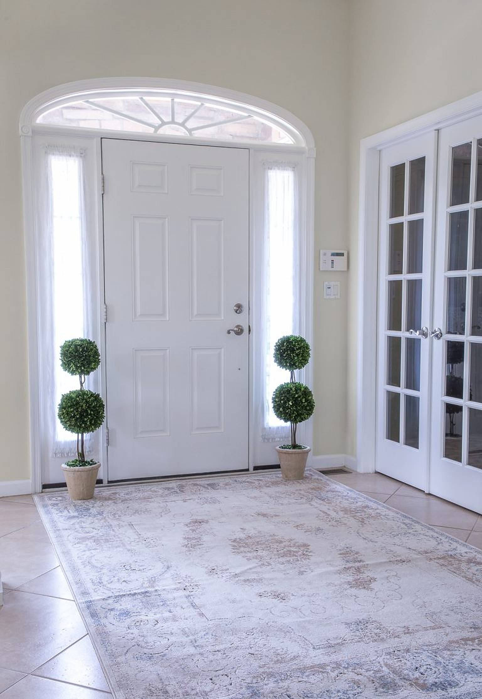 Elegant foyer with sculpted potted plants on each side of the door