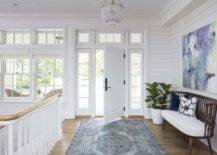 Entryway with large painting on the wall and blue rug