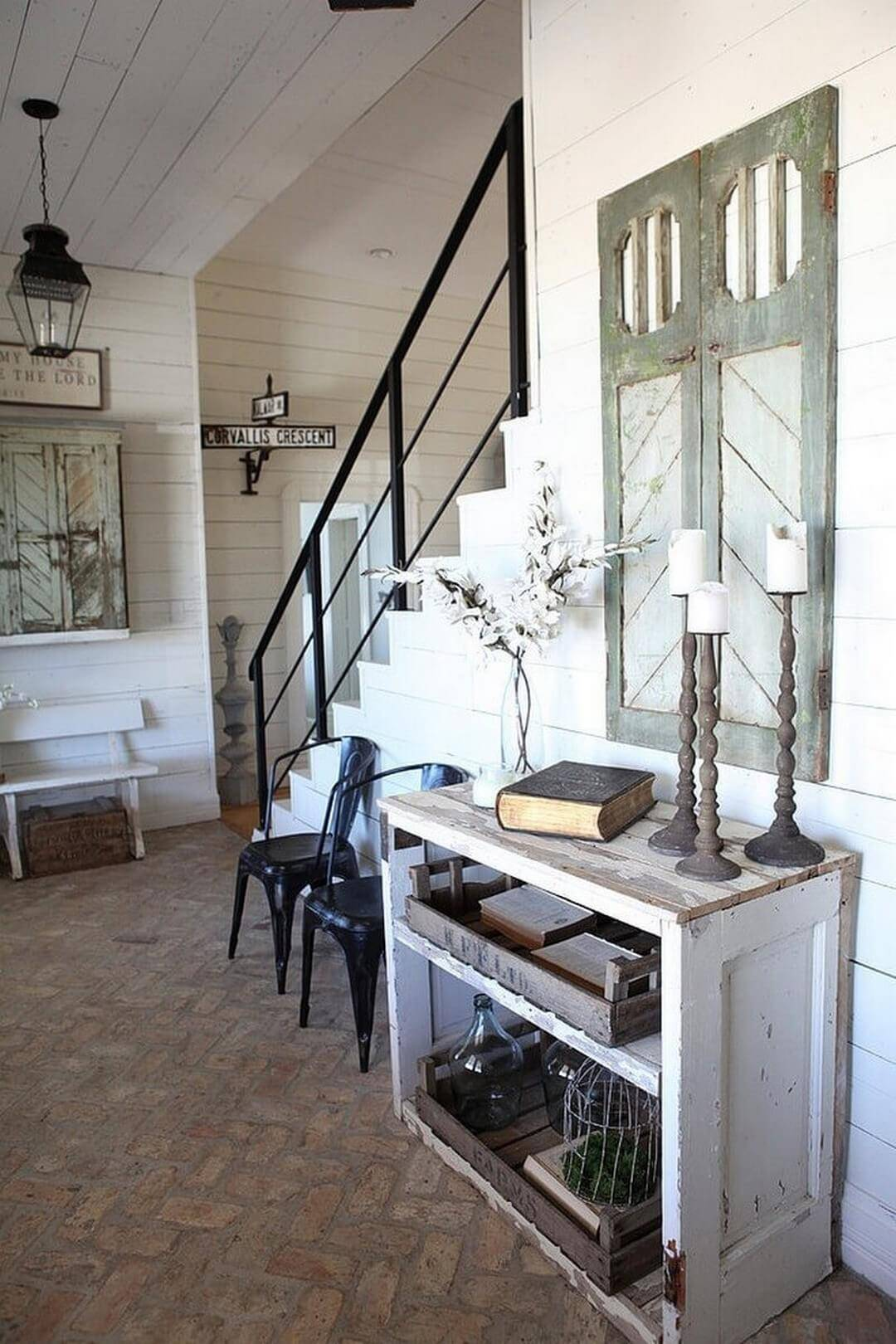 Entryway with wooden console and vintage window shutters on the wall
