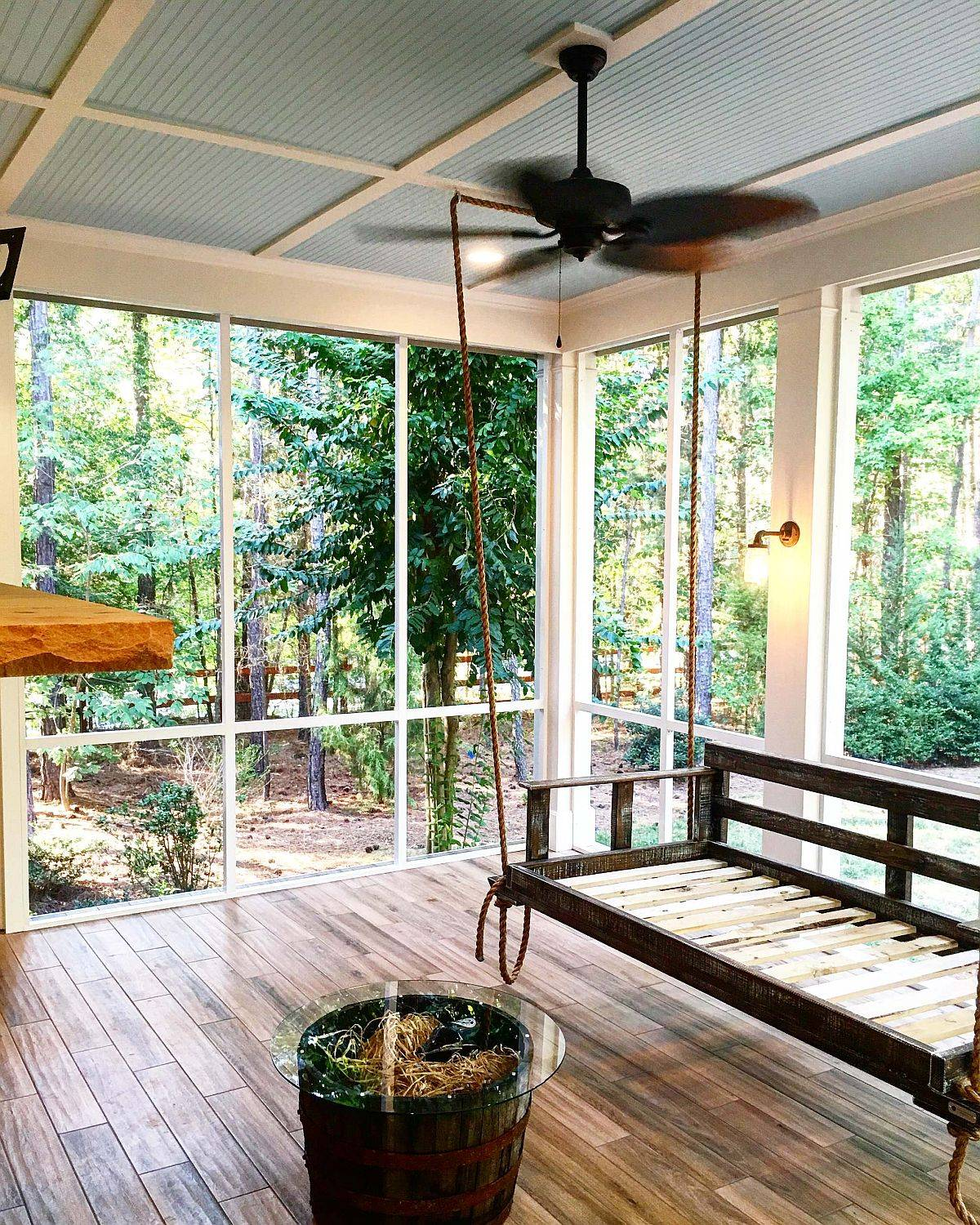 Gray ceiling and a tropical fan give thi shabby-chic porch a unique identity
