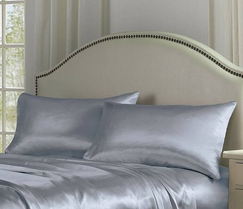 Grey satin sheet on bed with two pillows