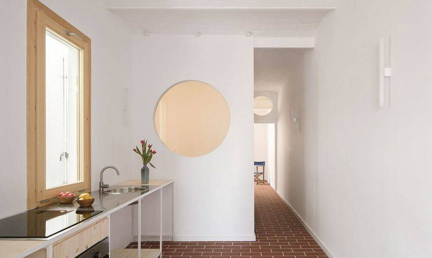 Dark Apartment in Barcelona Finds New Life with Open Rooms and Round Windows