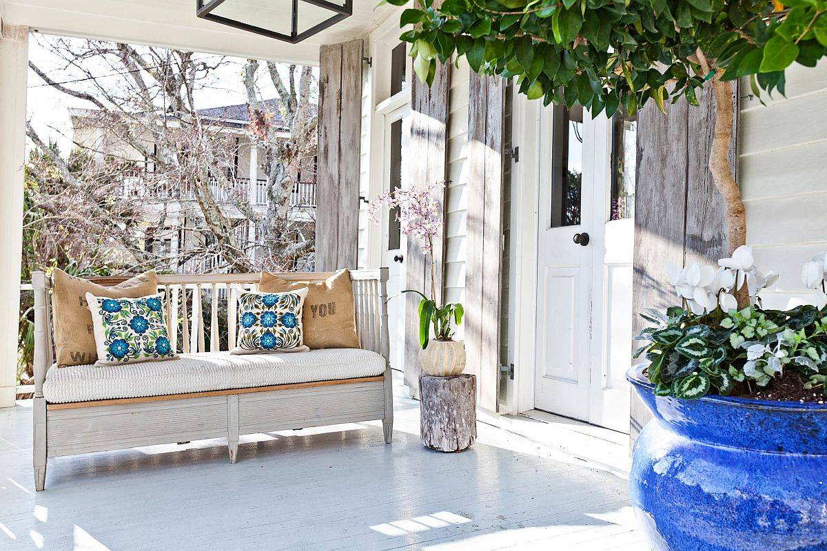 Lovely shabby chic porch in white with extended roof and a reclaimed wooden sofa for a relaxing evening