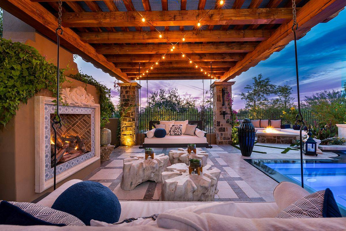 Luxurious shabby-chic porch with lighting and fireplace is an absolute showstopper