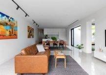 Open-plan-living-area-dining-space-and-kitchen-in-white-with-bright-wall-art-and-modern-decor-19778-217x155
