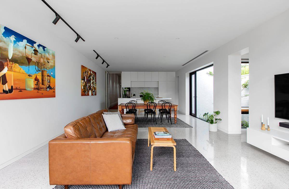 Open-plan-living-area-dining-space-and-kitchen-in-white-with-bright-wall-art-and-modern-decor-19778