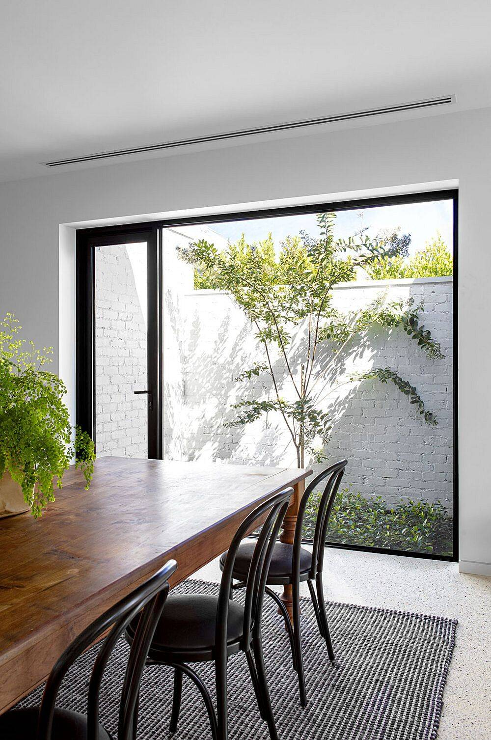 Picture window adds greenery and light to the dining area along with the kitchen