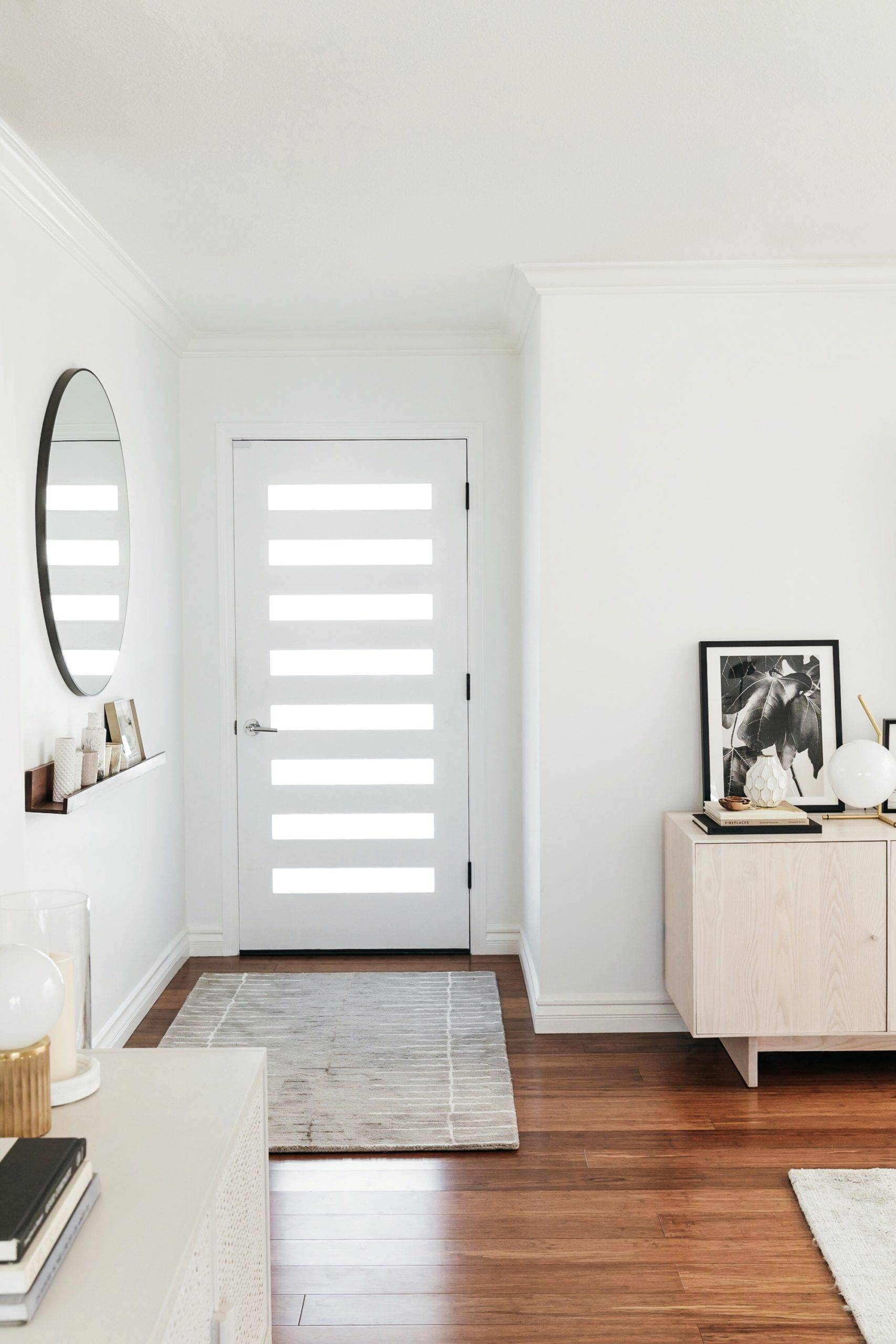 Round mirror hanging on wall beside white front door
