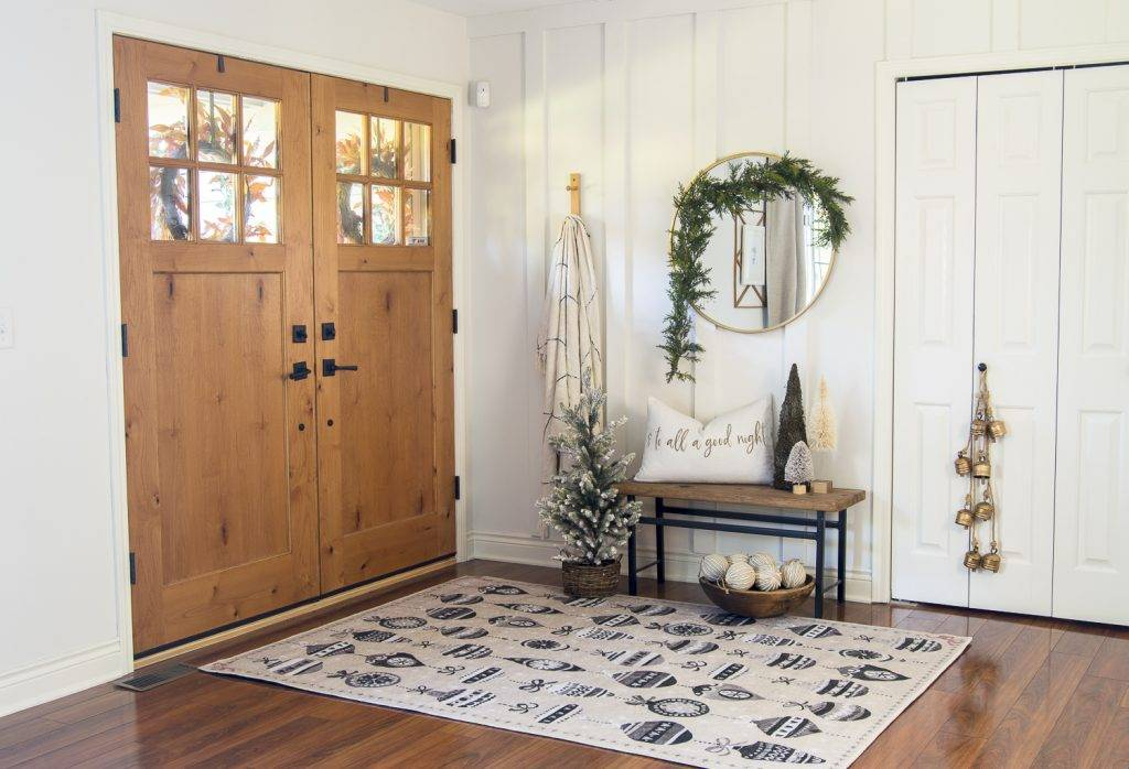 Round mirror with garland in entryway