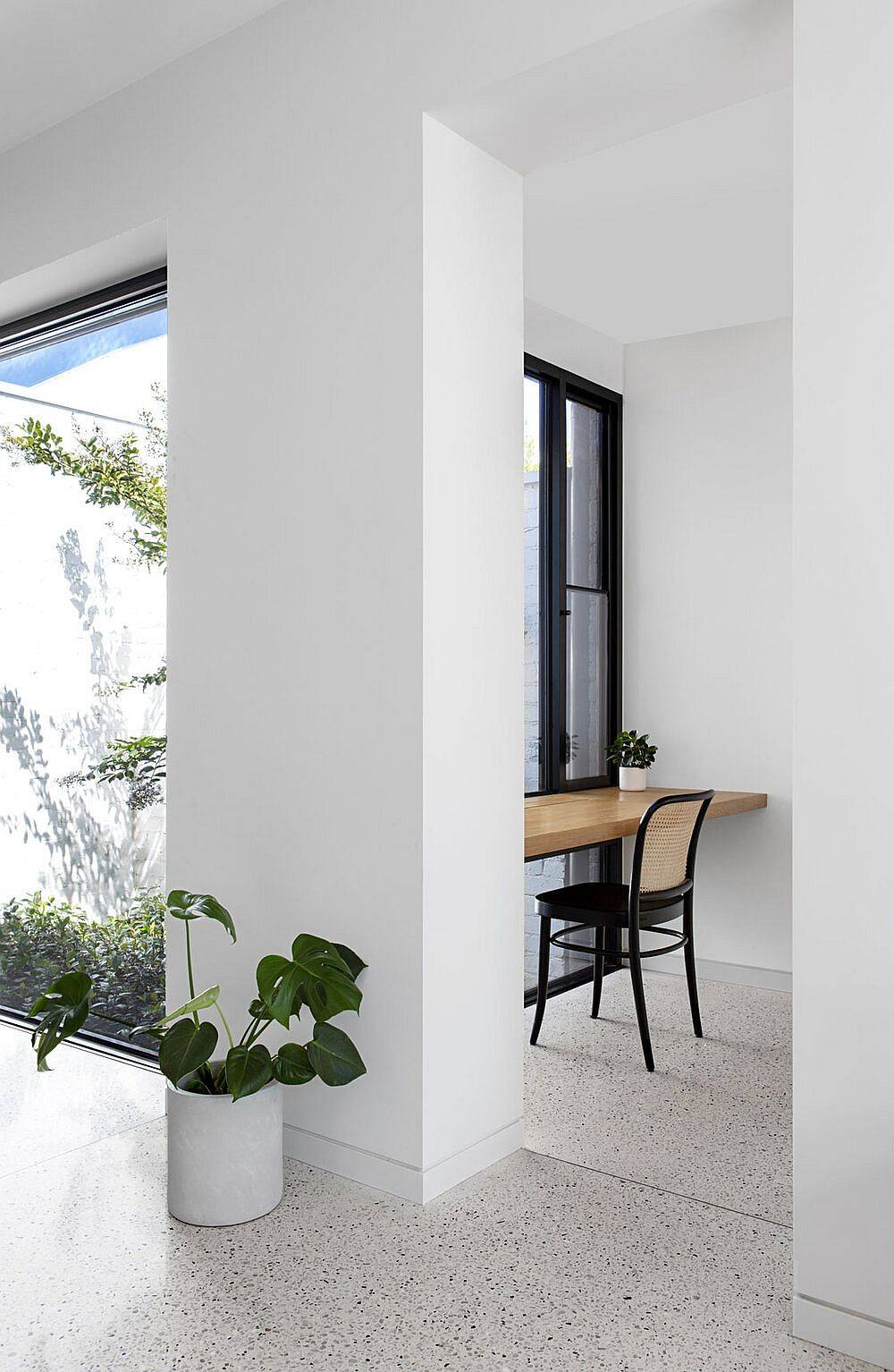 Slim-floating-wooden-desks-at-the-end-of-a-long-open-hallway-with-ample-natural-light-serve-as-workstations-23168