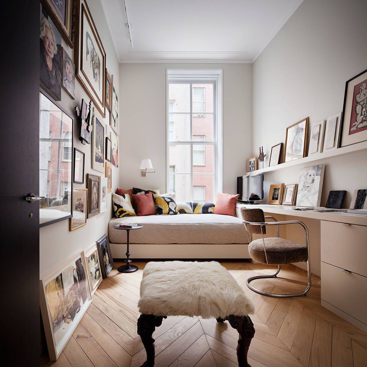 Small home office with platform bed and beautiful framed photographs and art pieces all around!
