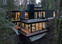 Two-story black house witg glass walls in the middle of the forest