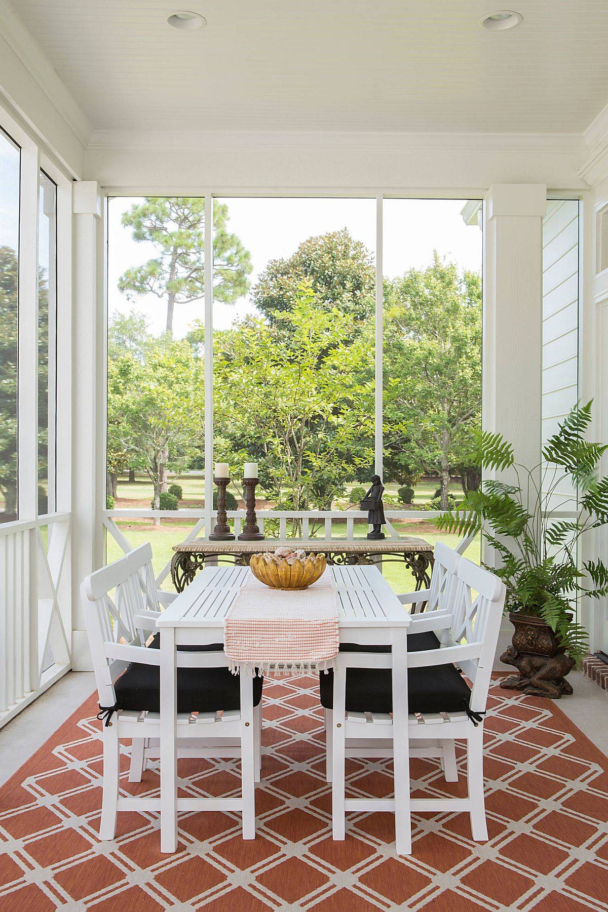 White shabby-chic porch with white decor and a rug that ushers in pops of terracotta