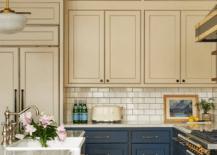 warm beige upper kitchen cabinets with dark blue lower cabinets