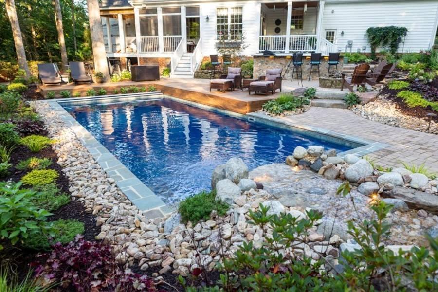 rock garden bordering square inground pool