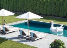 swan floating in pool next to patio furniture with shade umbrellas