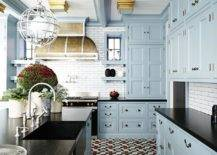 dark granite kitchen countertops with blue cabinets and patterned tile floor