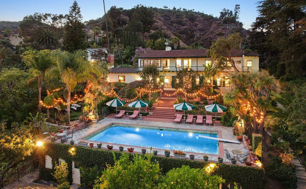 Backyard of the house with palm trees, pool area, multiple garders and sparkling lighting at the Hollywood Hills estate