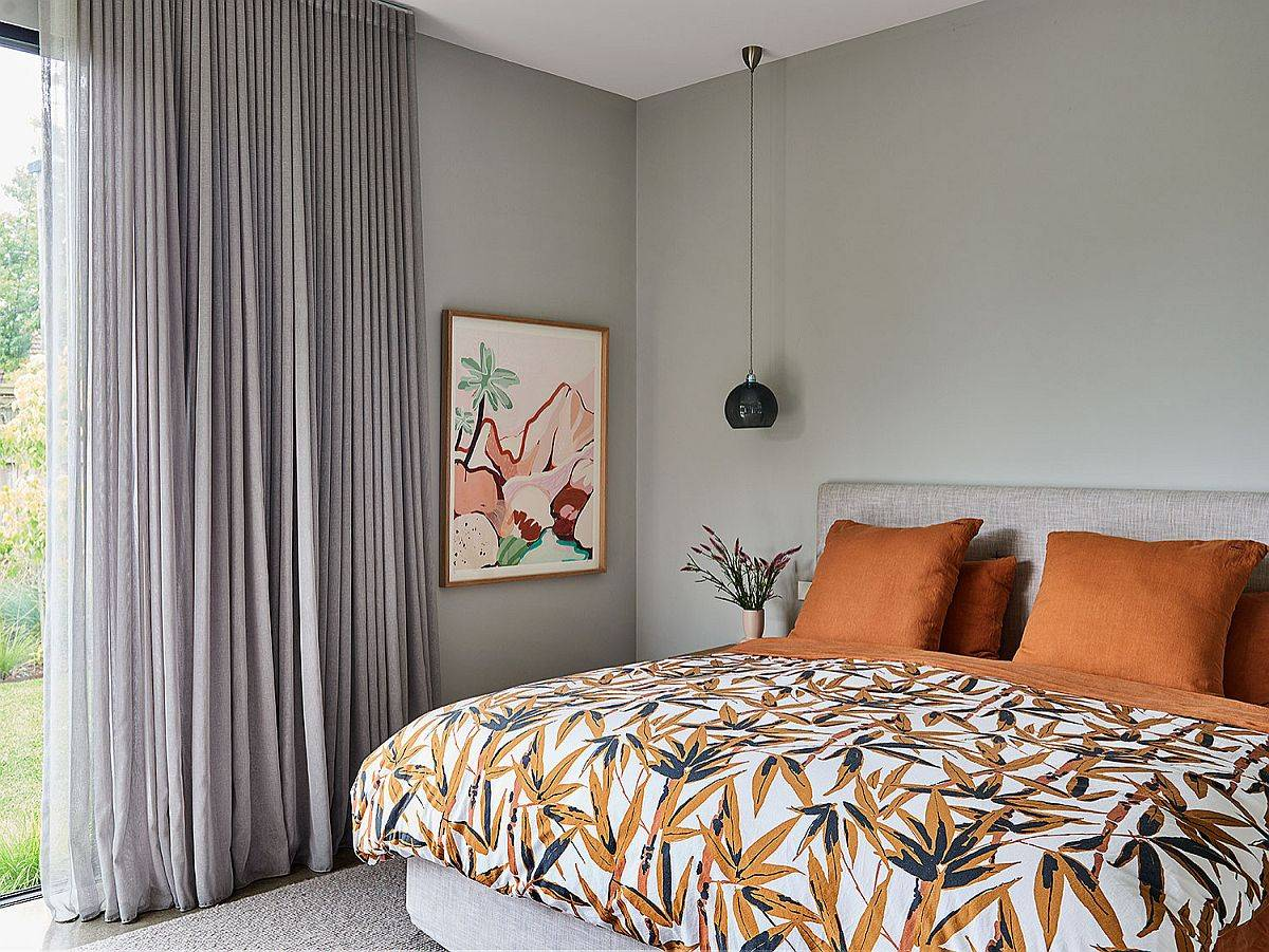 Bedding-and-accent-pillows-in-orange-bring-tropical-flavor-to-this-gray-bedroom-34508