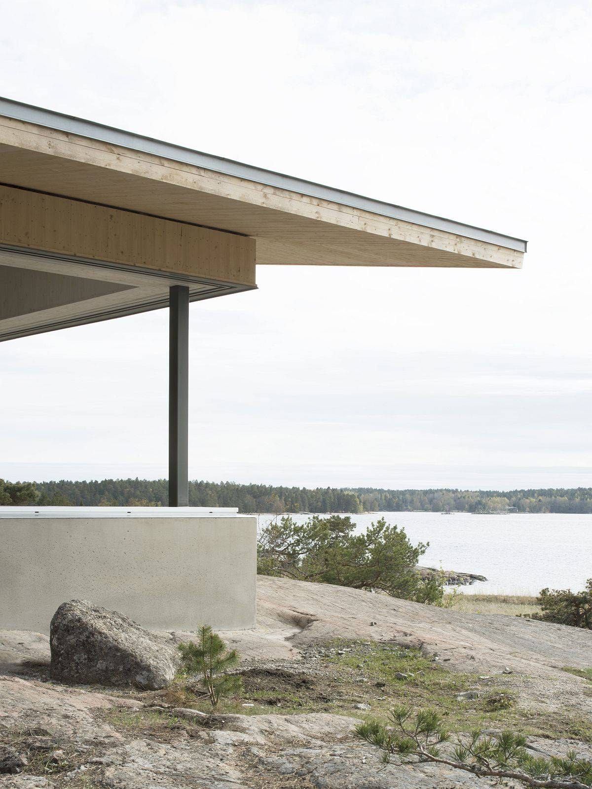 Concrete plinth around teh house creates a natural border with roof extending above it