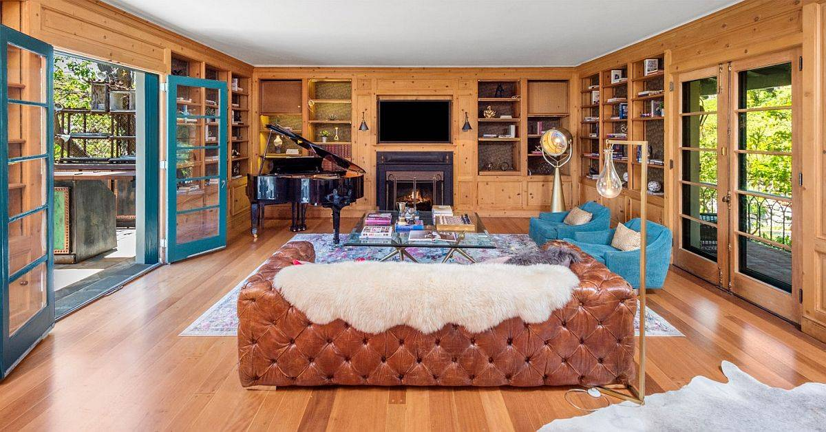 Family room of the home in wood with a pluh leather couch and a cozy fireplace