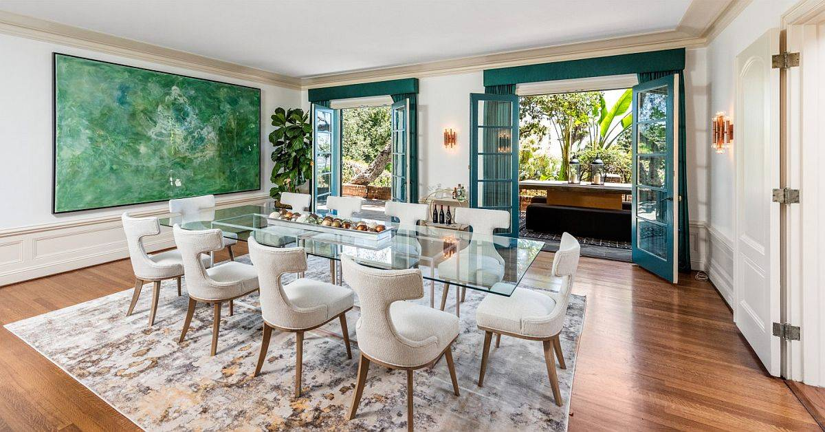 Modern dining room with glass dining table, green wall art piece and blue shutters