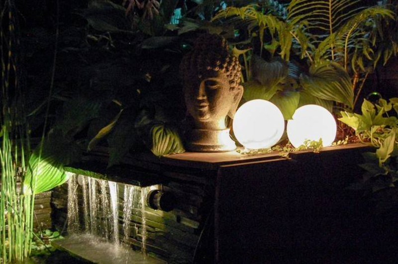 glowing orb lantern next to head sculpture and water feature