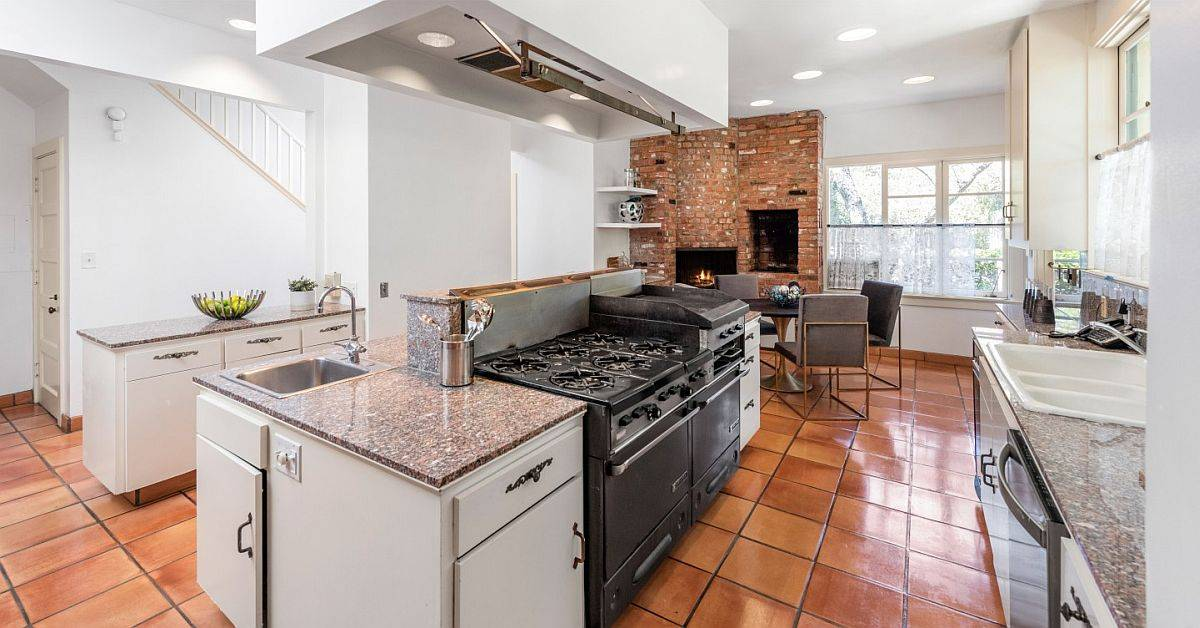 Saltillo-tile-kitchen-with-a-brick-wall-and-fireplace-at-the-other-end-and-cabinets-in-white-28488