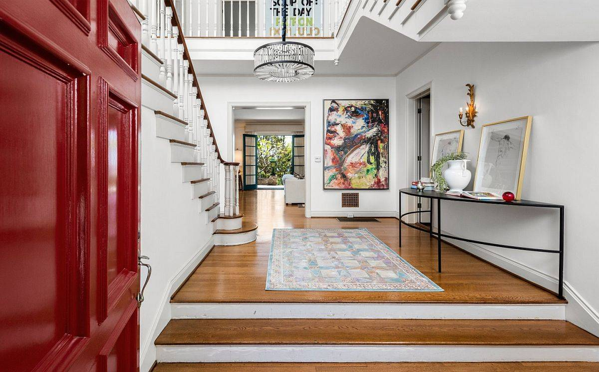 Spacious and stylish foyer of the home in white with a bright red door and smart lighting