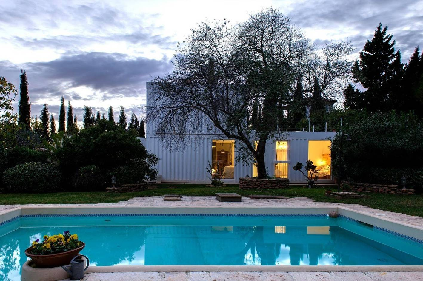 white two story container home at night with pool