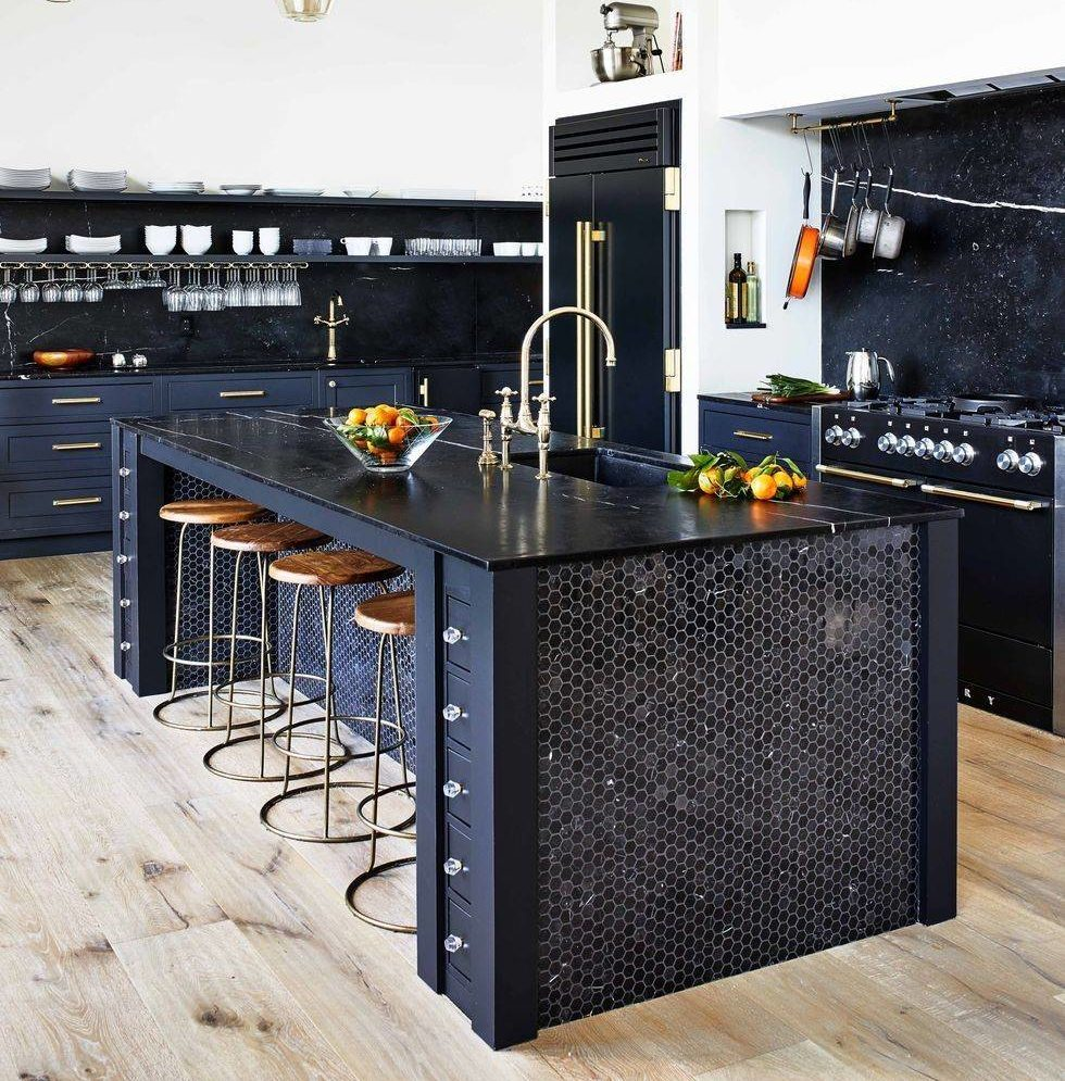 navy blue kitchen island and cabinets with gold fixtures