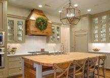 light wood kitchen island with curved chairs against beige cabinets