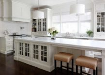 long white kitchen island with built in cabinets and low stools
