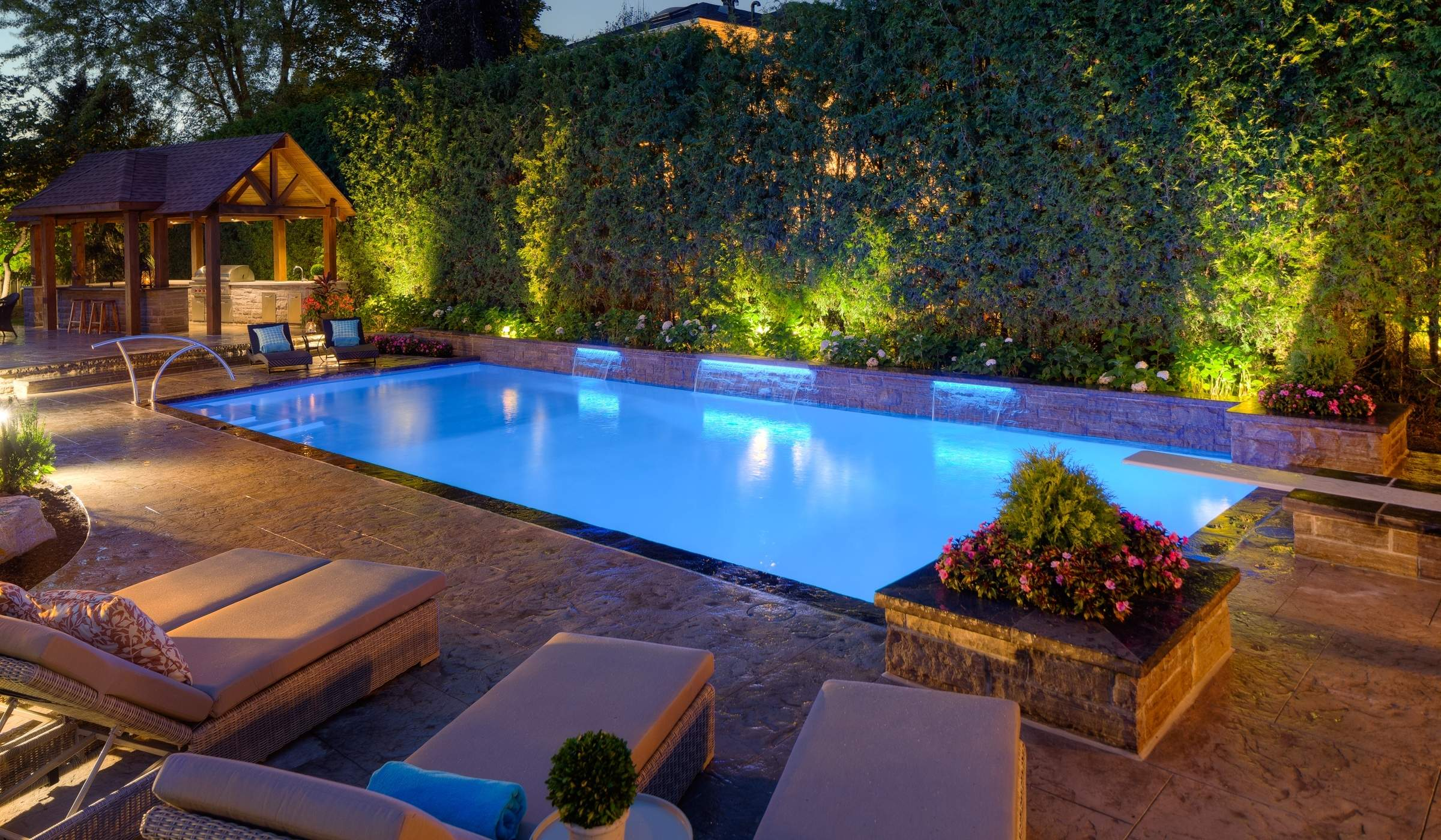 in ground pool at night lit up with stone patio and water feature