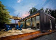 black steel container home with wooden patio