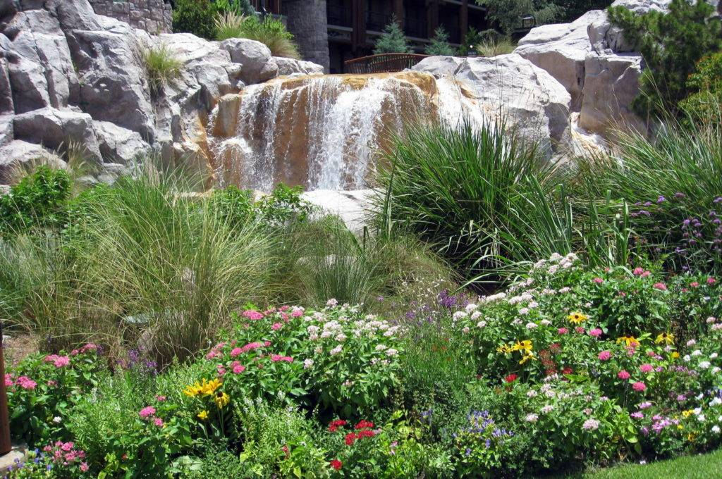 Softscape plants and flowers combine with hardscape stone waterfall feature