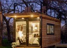 container home at night with bed and chair lit up