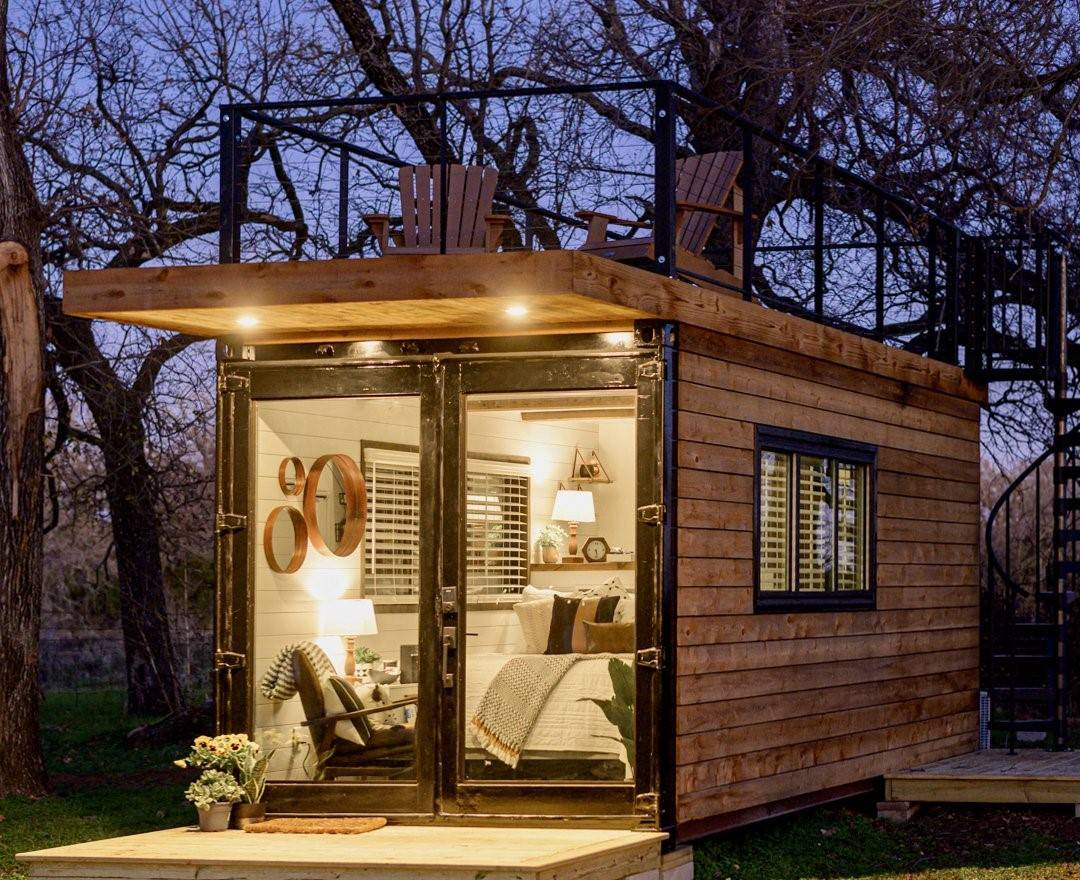 wooden container home with one bed and chair